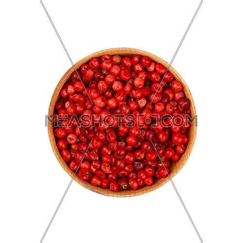 Close up one wooden bowl full of red pink pepper peppercorns isolated on white background, elevated top view, directly above