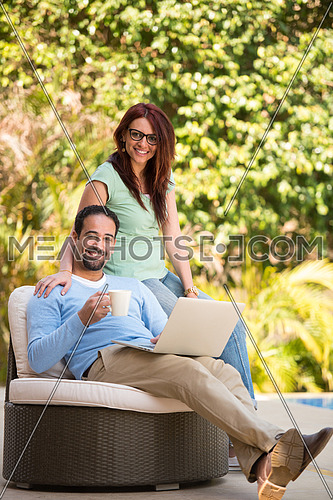 Young Middle Eastern couple enjoying your morning coffee in the garden sunny summer morning