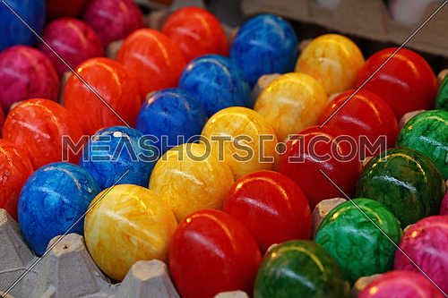 Close up many vivid colorful multicolor painted Easter chicken eggs in tray carton at retail display of farmers market, high angle view