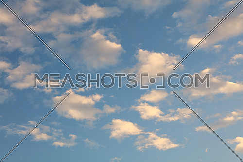 Beautiful cloudscape with bright white and pink clouds over blue sky at early sunset or late sunrise, low angle view