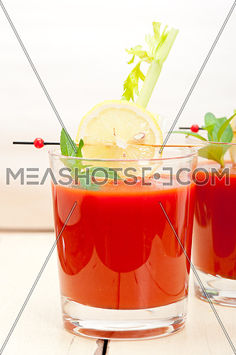 fresh tomato juice gazpacho soup on a glass over white wood table