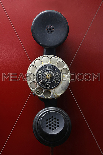 Early days of teachnology, wired handset with dial ring over red background