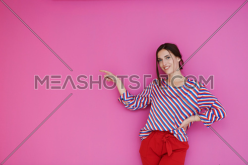 Happy surprised young female smiling broadly at camera, pointing finger away, showing something interesting and exciting on studio wall with copy space for your text or advertising content
