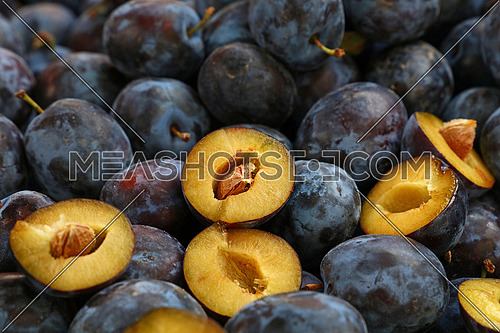 Heap of fresh ripe big blue whole plums and open cut halves close up at farmers market stall retail display, close up, low angle view