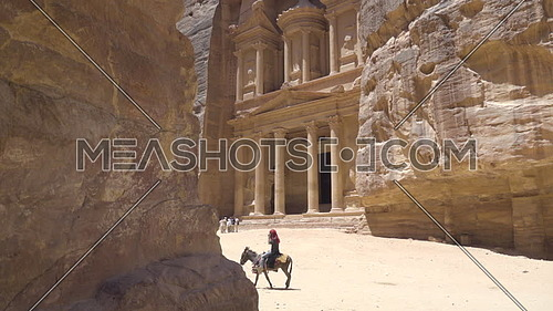 Pan down to Jordanian man riding a donkey in Petra