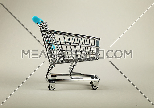 Close up empty toy metal supermarket shopping cart over grey background with copy space, low angle side view