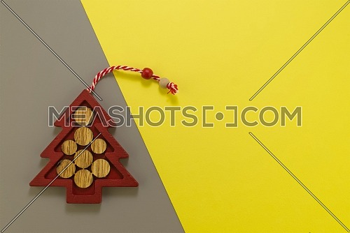 Stylized wooden Christmas tree on grey yellow background. Demonstrating trendy color of the year 2021. Illuminating yellow and ultimate gray