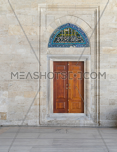 Wooden engraved door on stone wall and tiled marble floor, Sulaymaniye Mosque, Istanbul, Turkey