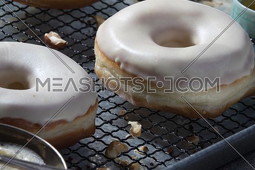 top side view  of white glazed donuts with walnuts aside