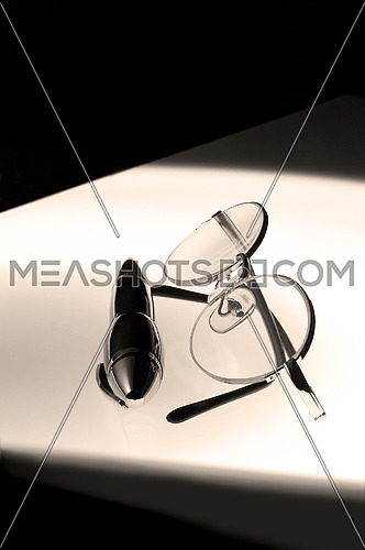 pen and glasses over white glass table