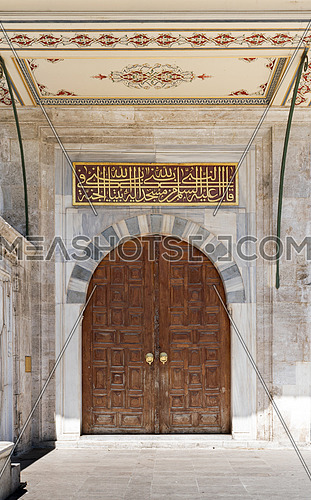 Wooden aged vaulted ornate door and stone wall at Sulaymaniye Mosque, Istanbul, Turkey