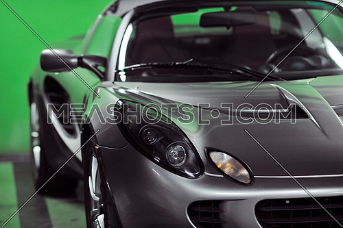 detail of sport silver car with green background