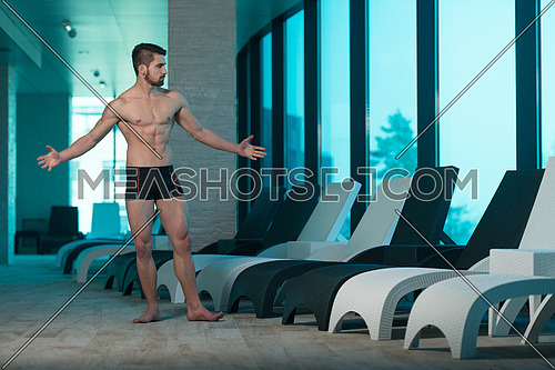 Young Muscular Man Flexing Muscles By Swimming Pool And Sun Loungers