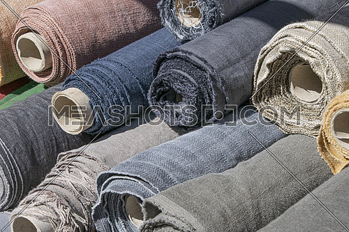 Close up assorted rolls of white, beige and brown flax linen fabric and canvas textile on retail market stall, high angle view