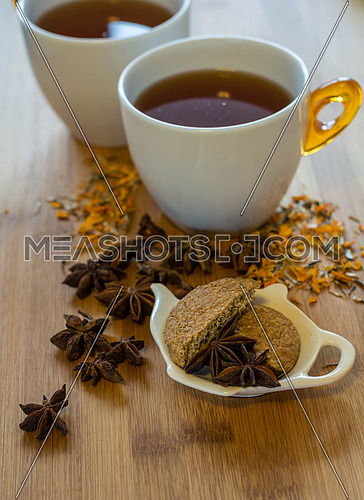 Tea, dried cinnamon, vegan cookies , and anise on wooden backgro