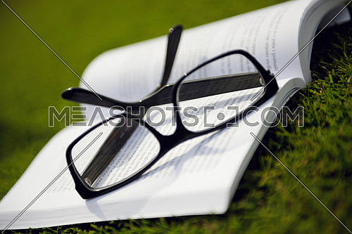Glasses on a book outside with grass inbbacground, education relax and study concept