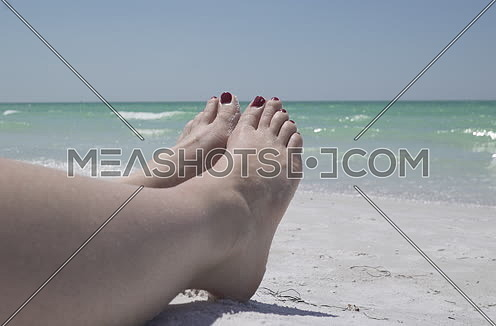 woman feet relaxing by the beach