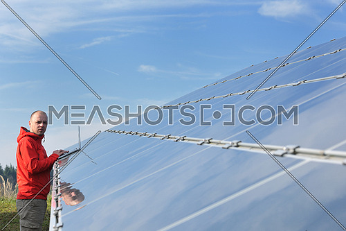 business man  engineer using laptop at solar panels plant eco energy field  in background