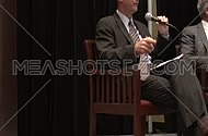 Medium shot for business man wearing a suit holding microphone and talking in Seminar.