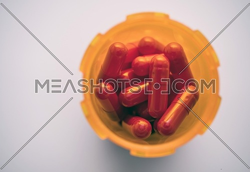 Bottle of red capsules seen from above, conceptual image