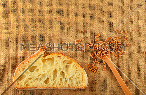Jute canvas with slice of white bread and handful of ripe grains, add your text