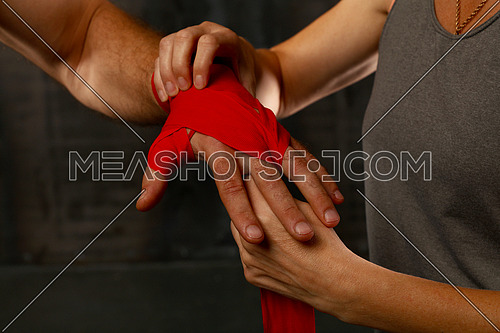 Close up woman trainer helps man boxer wrapping red hand wraps over wrists preparing for fight, over black background with copy space