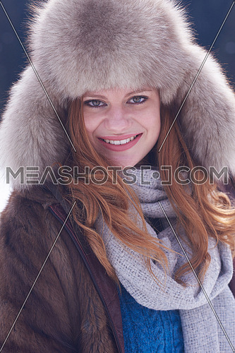portrait of beautiful young redhair woman in snow scenery with warm hat