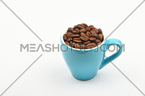 One small blue espresso cup full of roasted coffee beans over white background, close up, high angle view, personal perspective