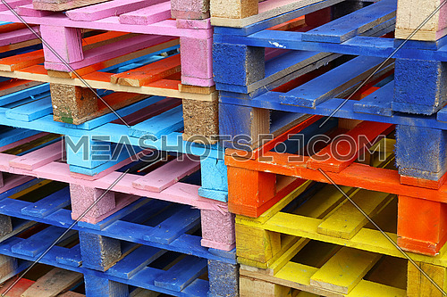 Close up stack of many vivid multicolor painted colorful wooden pallets, high angle diagonal view