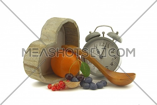 Culinary still life with old-fashioned alarm clock, pot, wooden spoons, cherries and orange, red currants and blueberries over an off white background with copy space