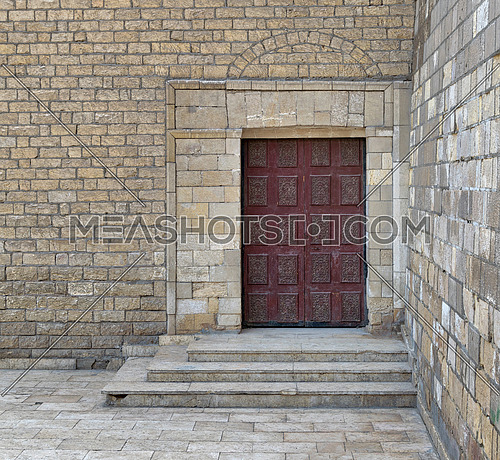 Wooden ornate engraved red door on bricks stone wall and deck stairs, exterior of Al Hakim Mosque (The Enlightened Mosque), Cairo, Egypt