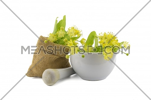 Bowl and small hessian bag of freshly picked yellow linden flowers and leaves, also called tilia and lime, for making a healing tisane or tea over a white background