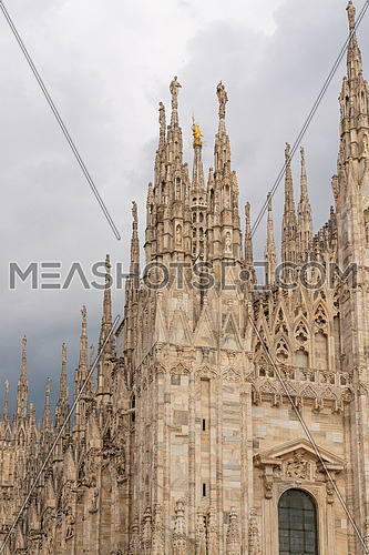 """Details of Duomo with the golden statue name """"Madonnina"""" on the top,overcast sky."""