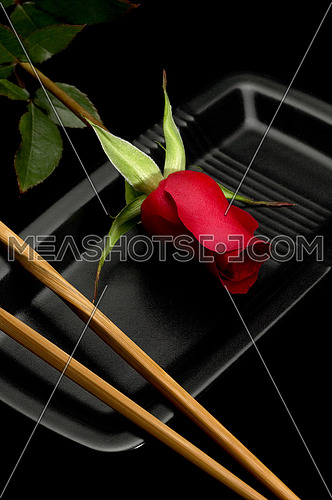 red rose on a japanese black plate with chopsticks over black