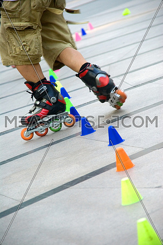 young guy skating slalom around colorfull cones