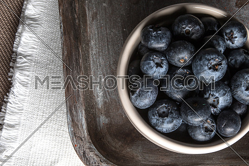 A bowl of blueberries with white burlap