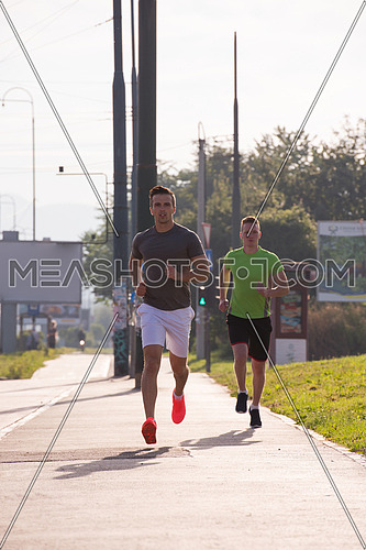 athletic young men enjoy running while the sun rises over the city