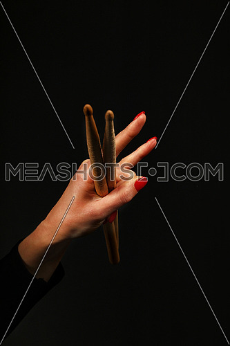 Woman hand holding two drumsticks with devil horns rock metal gesture sign over black background, side view