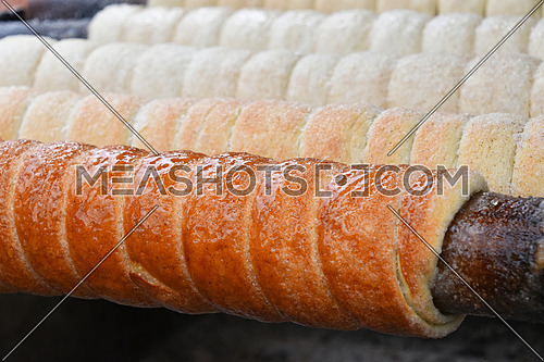 Close up sweet Trdelnik baking on grill, this spit cake is popular in Europe, Austria, Hungary, Slovakia and Czech, especially in Prague