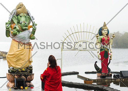 A kneeling woman pray in front of a Hindu deity, Grand Bassin Mauritius