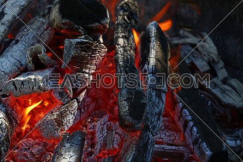 Blaze of bonfire, wood fire flame heat spires burning in fireplace with smoke close up
