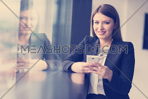 businesswoman speeking on phone beside window of modern office