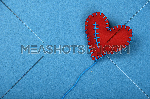 Felt craft and art, one handmade red stitched toy heart with thread on blue background