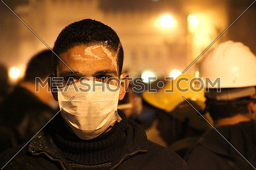 a man wearing a mask and looking to camera during a protest at night