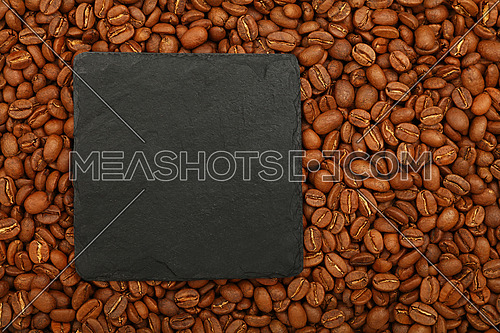 Close up one blank empty black slate board sign over brown roasted coffee beans background