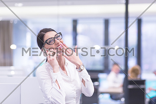 female manager using cell telephone in startup office interior