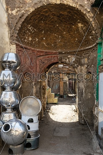 Arched passage between shabby houses with Egyptian traditional aluminum utensils stacked by wall in old Cairo city, Egypt on daytime