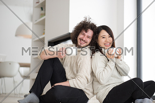Young romantic multiethnic couple sitting on the floor in front of fireplace at home, talking and drinking coffee at cold winter day