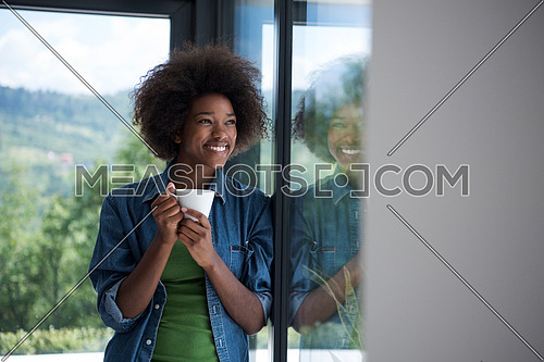 Beautiful young african american woman drinking coffee and looking through a window in her luxury home