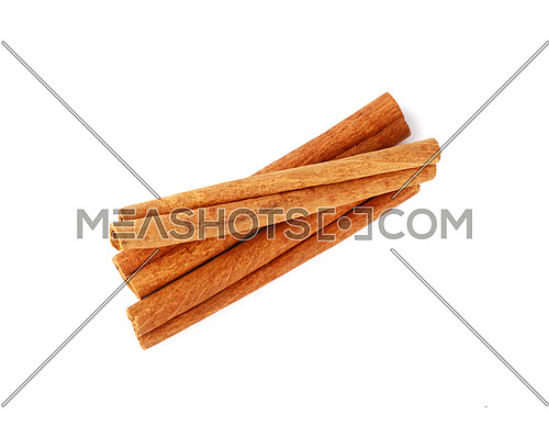 Close up heap of three cinnamon sticks isolated on white background, elevated top view, directly above